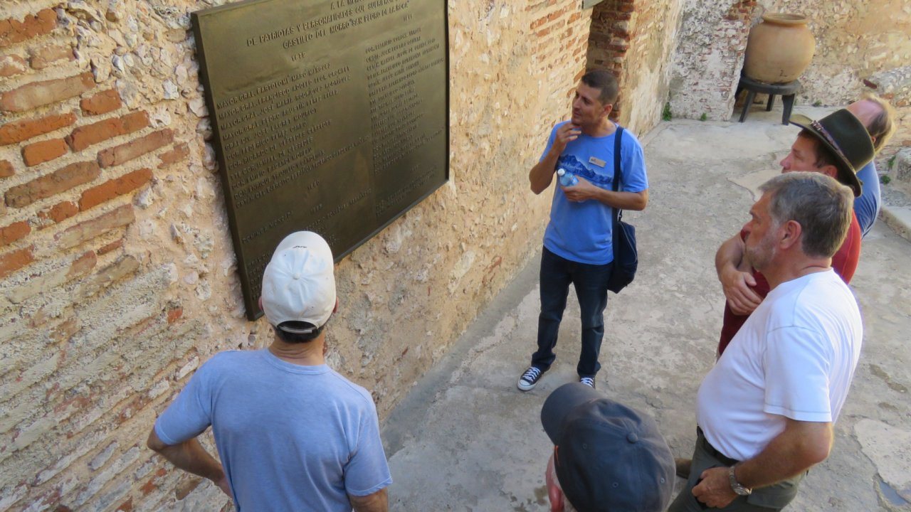 visitors looking at sign in Cuba